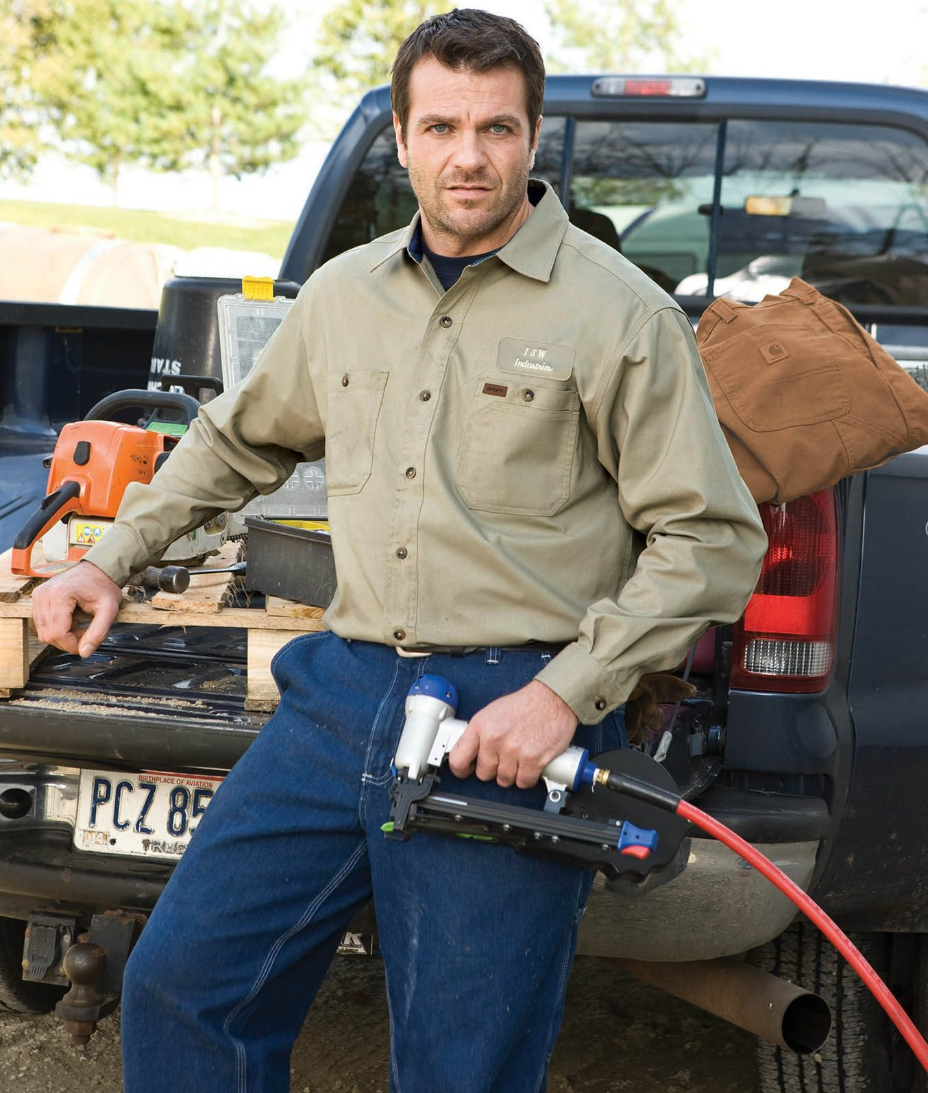 Contruction worker resting on a pickup truck tailgate with a nail gun in hand in a light brown Carhartt shirt and blue jeans