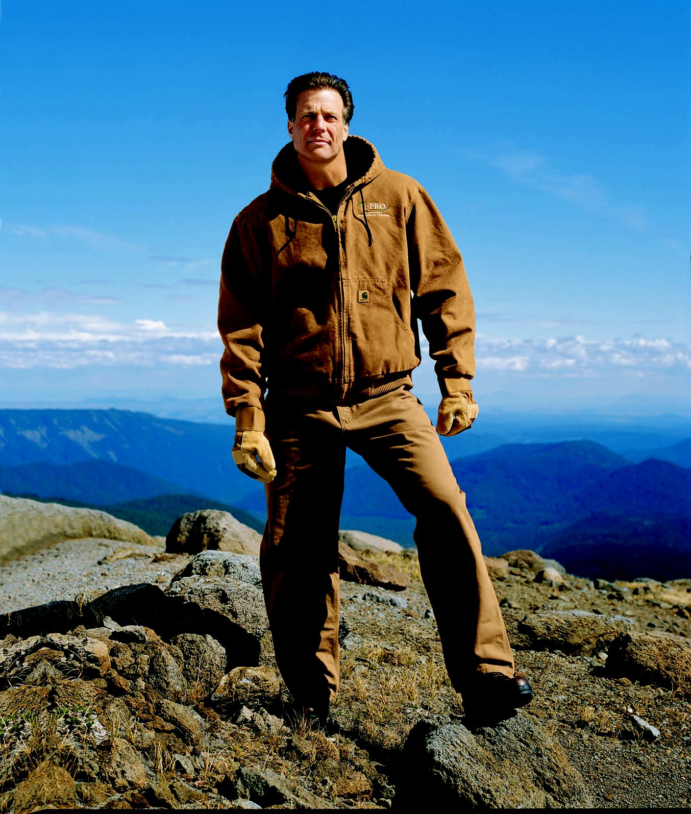 Outdoor worker on a mountain in brown Carhartt jacket and pants