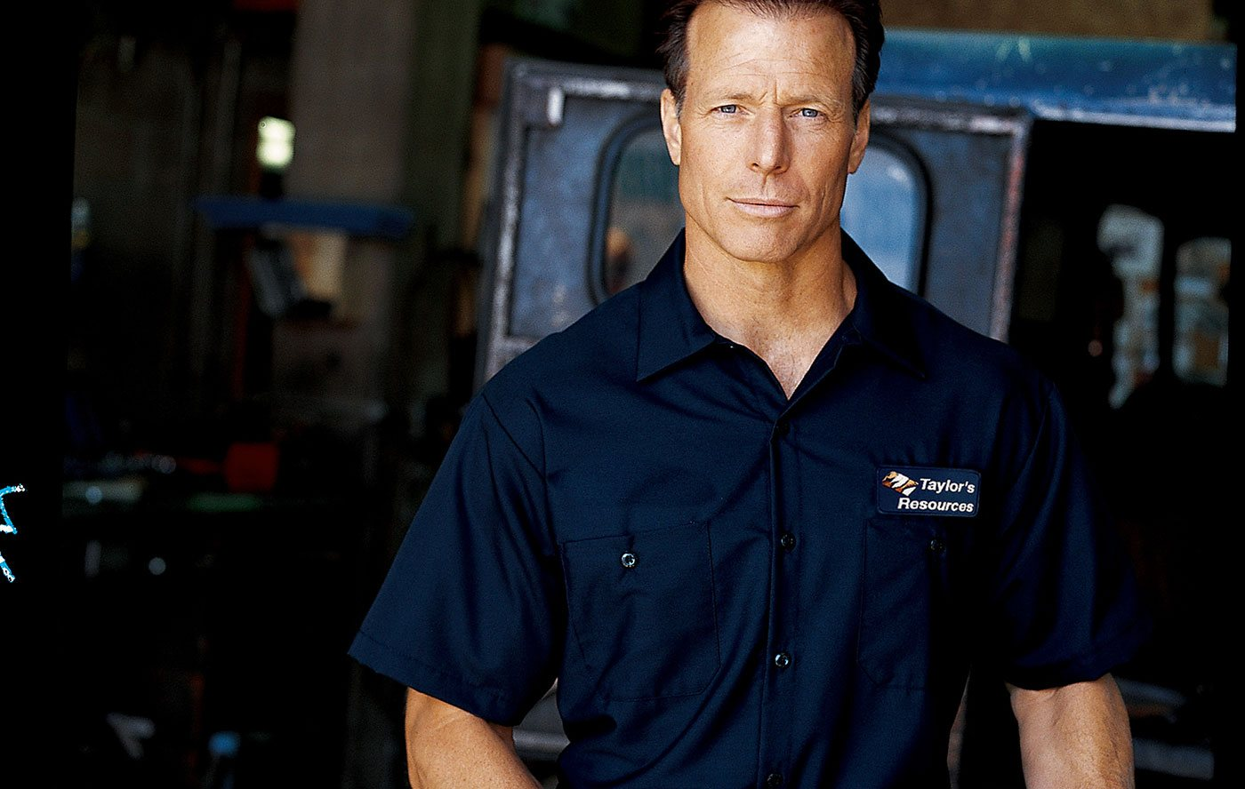 Mechanic in automotive uniform with his company's logo on the button up blue shirt