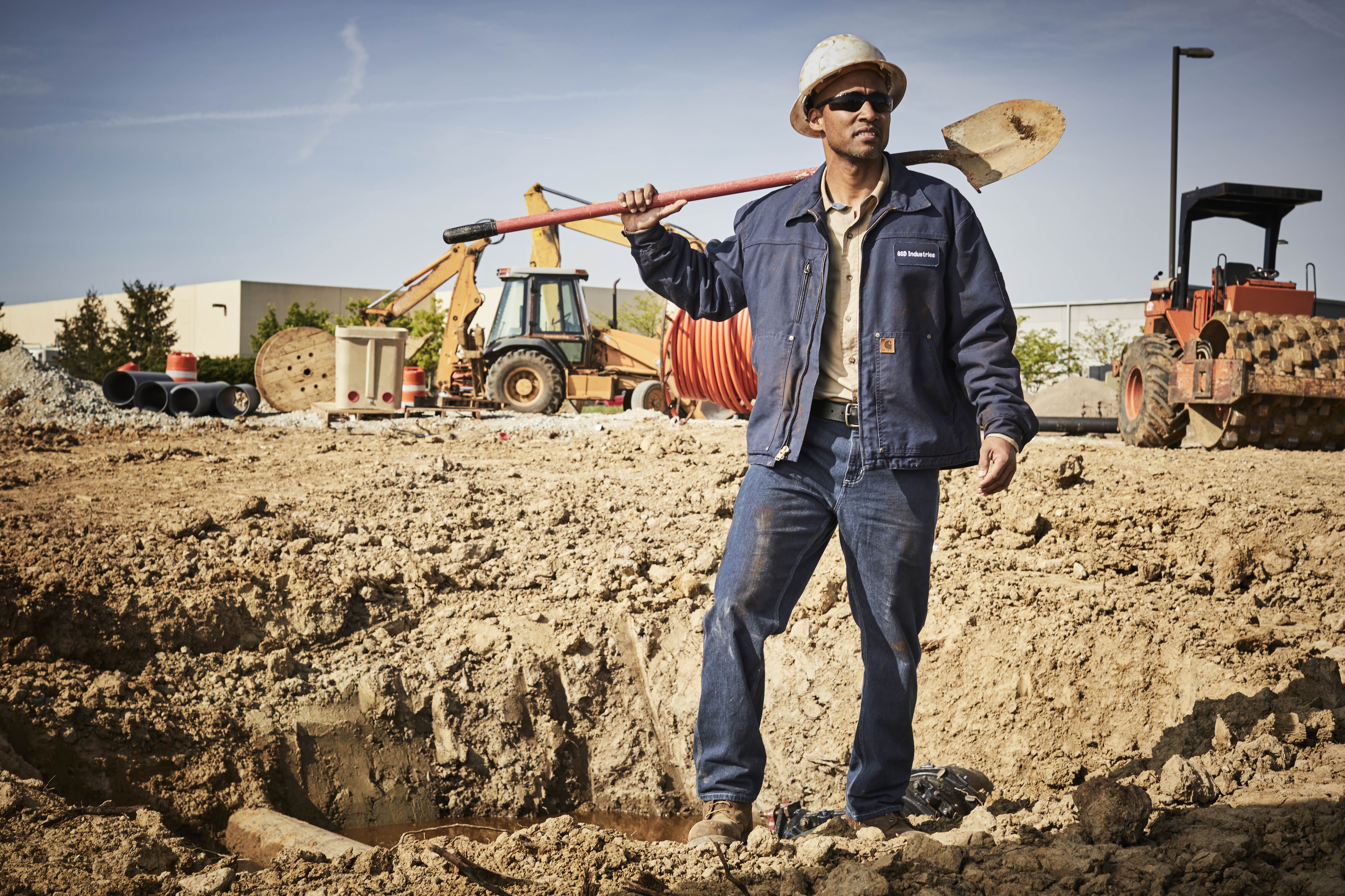 Construction worker on site in a Carhartt jacket, light brown button up shirt and jeans holding a shovel