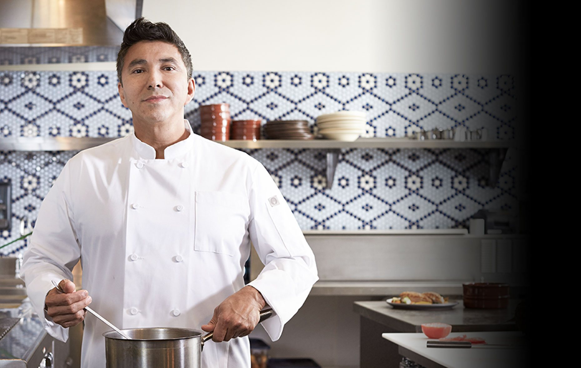Chef in a kitchen wearing a Chef Works Signature white chef coat