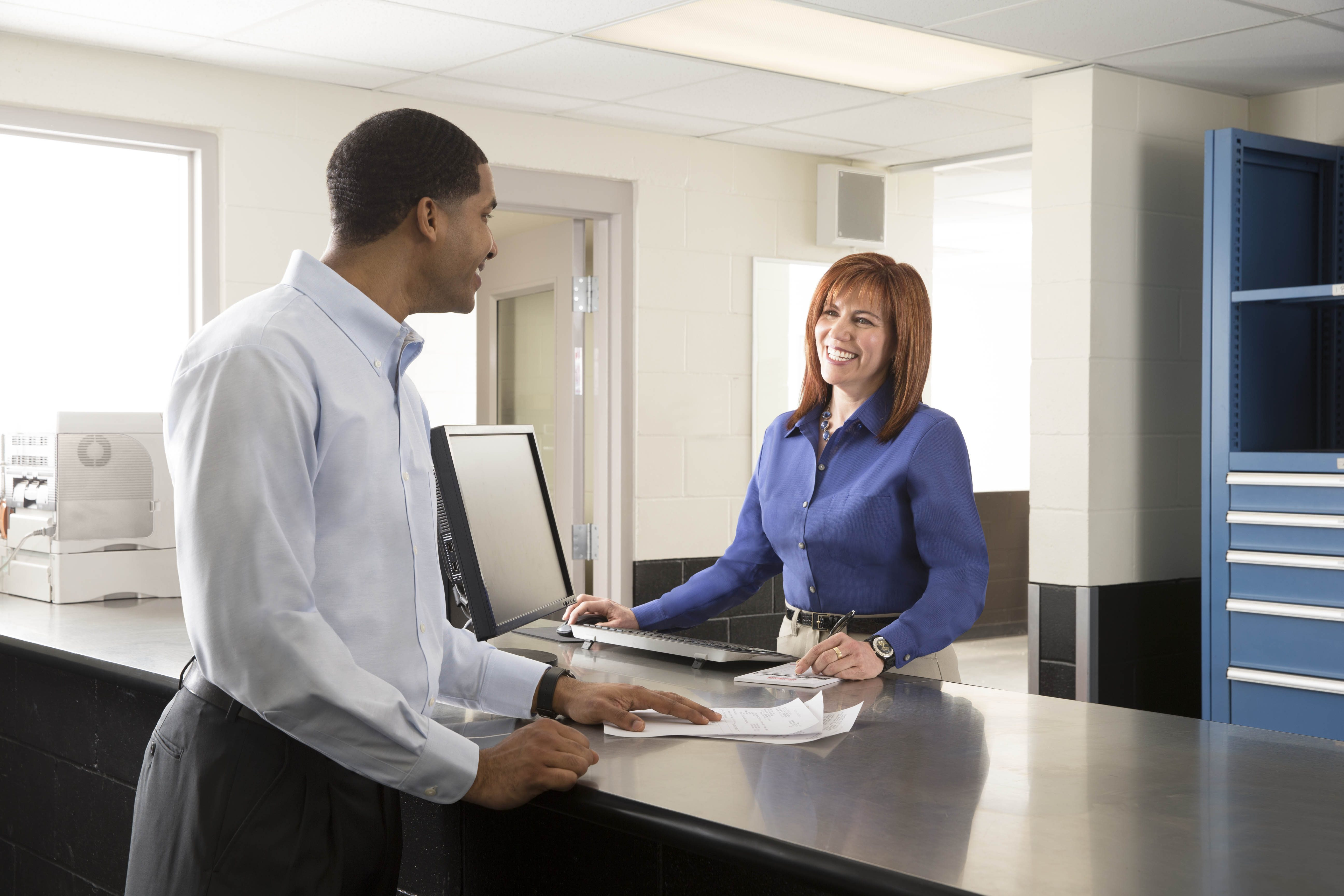 Woman in a hospitality uniform (blue dress shirt) checking in a customer at the front desk