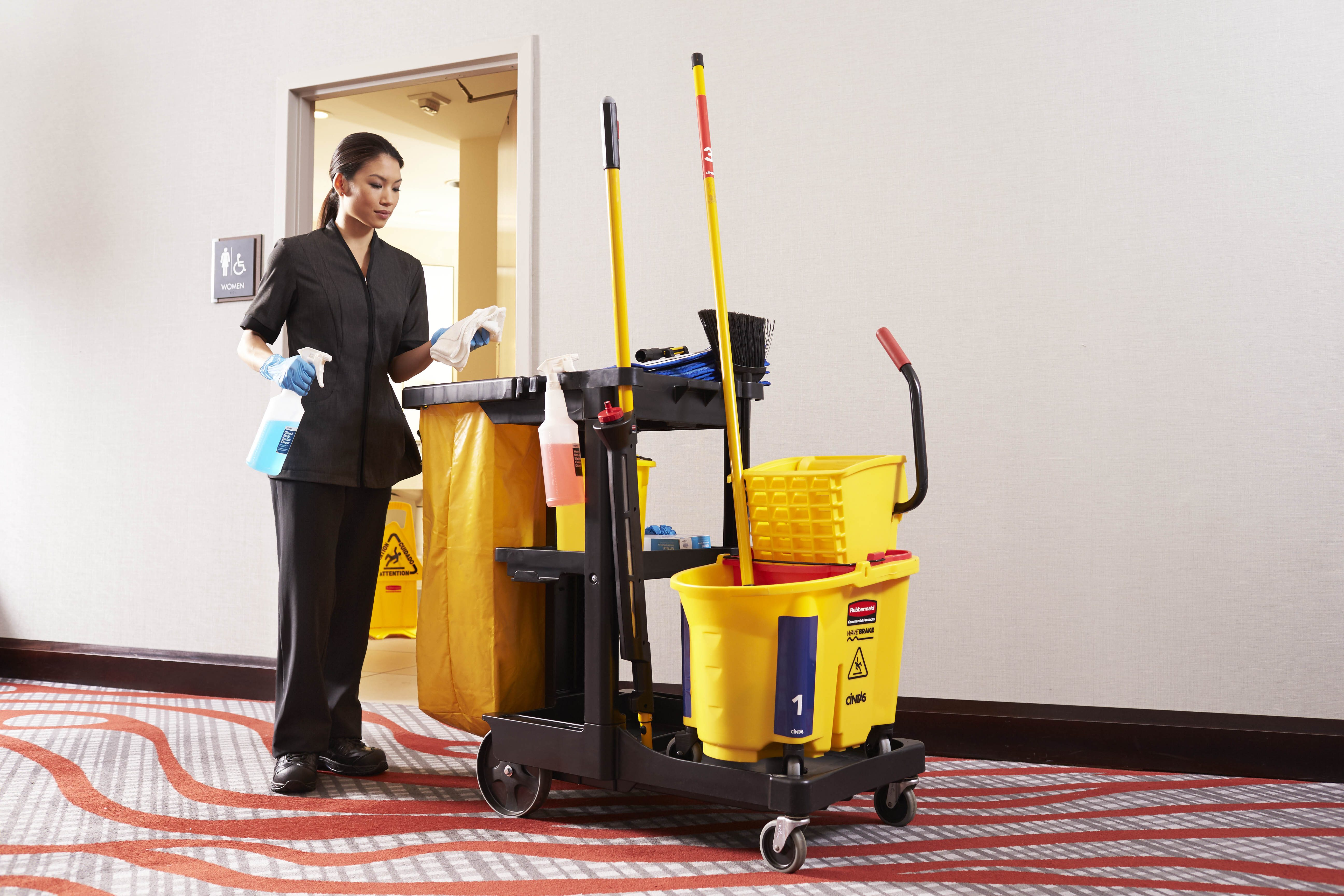 Woman in a black housekeeping uniform holding a spreay bottle by a janitorial supplies cart