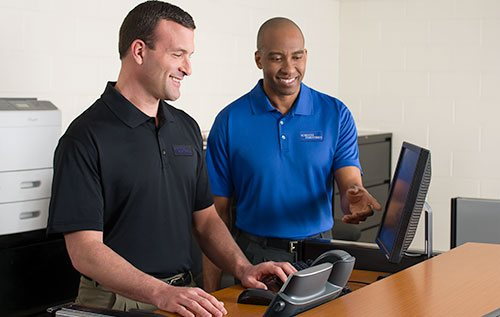2 IT workers in custom logo embroidered on their blue and black polos