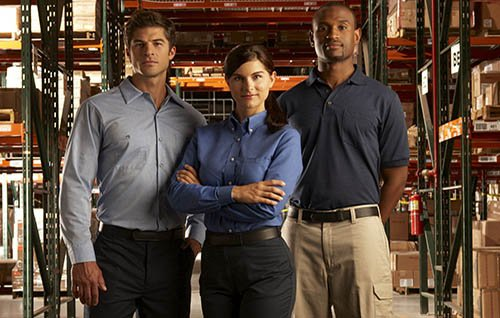 1 woman and 2 men in a warehouse in button up shirts and nice slacks