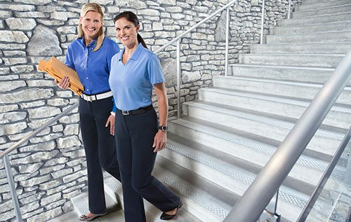 Women in Cintas rental workwear for women on stairs in a lobby